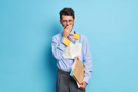 Photo of exhausted man yawns after long hours of working prepares financial report wears formal clothes poses indoor against blue background. Tired student busy with course work. Occupation concept
