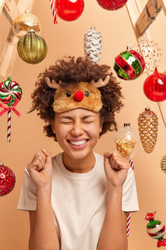 Glad dark skinned woman with curly bushy hair raises clenched fists and celebrates success prepares for celebrating Christmas wears casual clothing poses against New Year toys hanging around