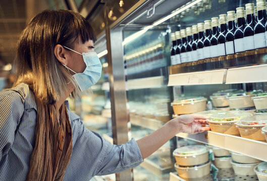 Asian woman wearing mask taking well covered salad at buffet during pandemic