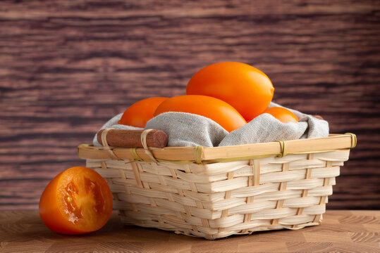 Yellow ripe tomatoes in a wooden bowl on a wooden background
