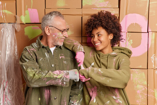 Cheerful multiethnical woman and man make fits bump work as team discuss home decoraton paint interior walls in house look happily at each other. Team work concept. People and repair concept