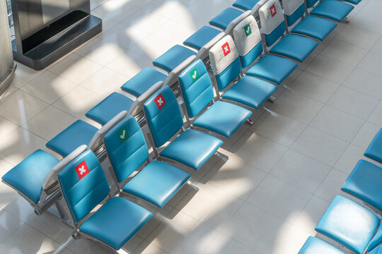 Social distancing for travel safety with seat allocation and sitting distance allowance warning sign on chairs in airport or bus terminal during covid-19, coronavirus pandemic
