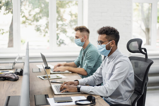 Young people professionals working in office wearing medical protective masks, Colleagues using laptops in coworking, Selfcare, coronavirus COVID-19 protection, social distancing, healthcare concept