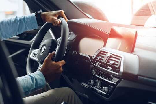 Male hands holding steering wheel of a car