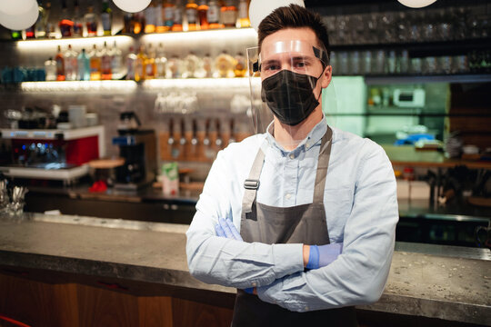 the waiter takes delivery and works in a small restaurant, wearing a mask and glass protective against the coronavirus pandemic and bacteria. does his business while working in the city center.