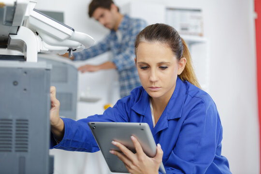 technician holding tablet while working on electrical appliance