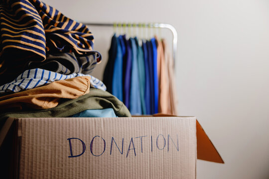 Donation Concept. Preparing Used Old Clothes from Wardrobe Rack into a Donate Box. Focus on Text