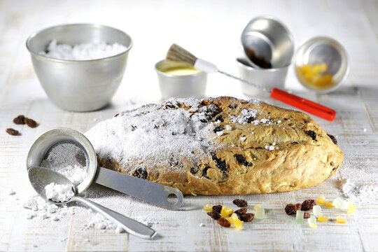 freshly baked traditional Saxon Christmas Stollen with some baking ingredients to be finished with powdered sugar