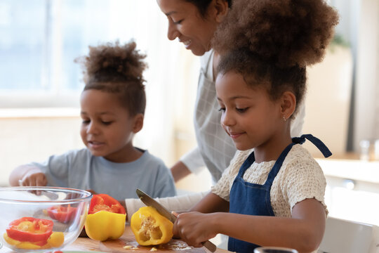 You are doing great. Satisfied smiling young black foster mother, babysitter, adult elder sister watching two small kids adopted son daughter, boy girl wards or younger siblings cooking vegetable dish