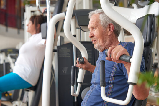 Older man doing strength exercise at gym. Mature man working out at fitness club. Resistance exercise at gym.