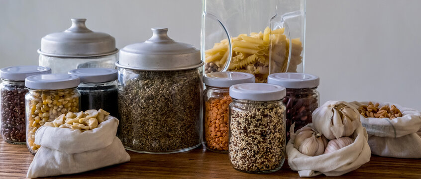 Assortment of uncooked grains, cereals, pasta and nuts in glass jars and cotton bags on wooden table. Eco-friendly organic bio bulk kitchen products. Zero waste sustainable plastic free lifestyle