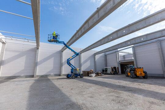 Warehouse construction. Worker on mobile elavating work platform
