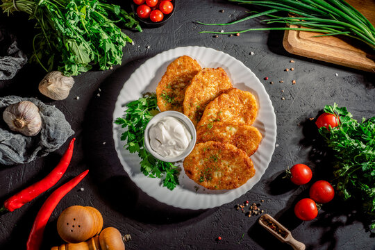 Potato pancakes served with fresh cream and spring onion on dark background