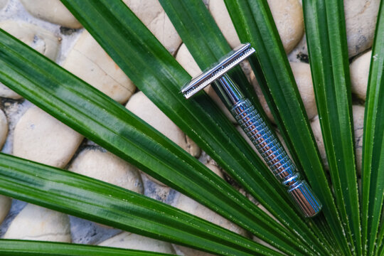 Reusable steel double edged eco-friendly safety razor on stone background with tropical palm leaf. Zero waste sustainable plastic free lifestyle