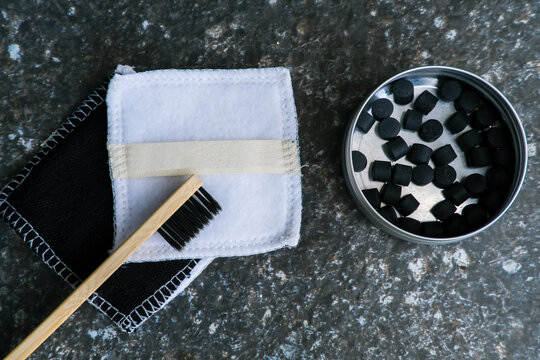 Eco-friendly oral care bathroom accessories on minimalist stone background. Biodegradable bamboo toothbrush with charcoal solid toothpaste tablets. Zero waste sustainable plastic free lifestyle