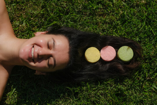 Young woman laying on the grass with natural eco friendly solid shampoo bar or conditioner on her hair. Zero waste and sustainable plastic free lifestyle