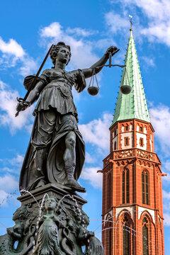 Gerechtigkeitsbrunnen auf dem Frankfurter Römerberg mit der Kirchturmspitze der Alten Nikolaikirche im Hintergrund