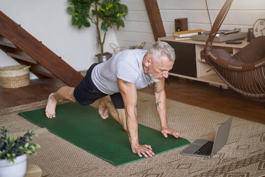 Sporty and healthy middle aged man exercising in the living room of his modern apartment, watching online video tutorial on laptop
