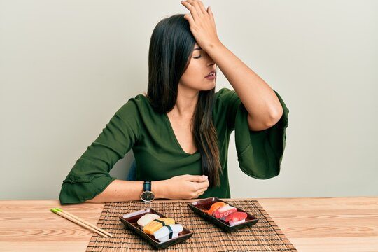 Young brunette woman eating sushi sitting on the table surprised with hand on head for mistake, remember error. forgot, bad memory concept.