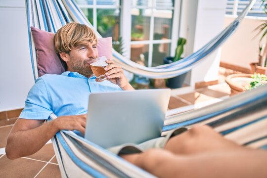 Middle age handsome man at the terrace of his house relaxing lying on a hammock working with laptop and drinking a fresh beer