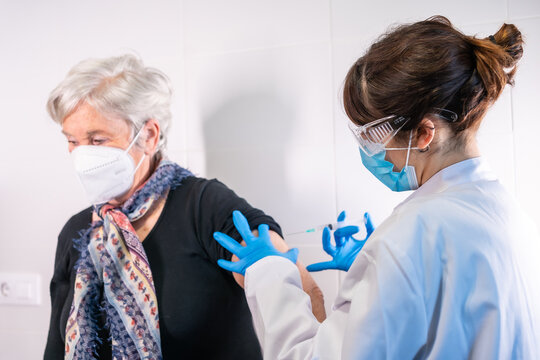 An elderly woman receiving the injection of the coronavirus vaccine by a doctor to receive the antibodies, immunize the population. side effects, risk people, antibodies, new normal, covid-19.
