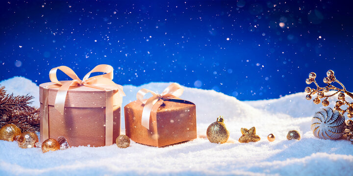 Winter holidays background with eco-friendly gift boxes and golden Christmas ornaments on snow