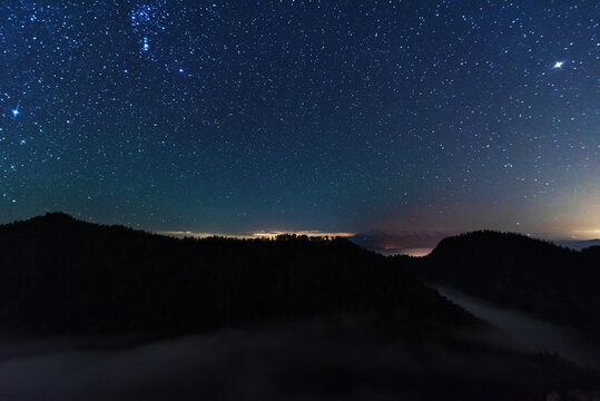 A beautiful starry night in the mountains on top with beautiful scenery and fog.