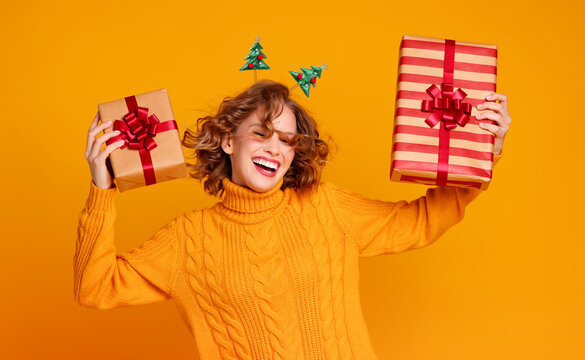 Young woman dancing with Christmas presents