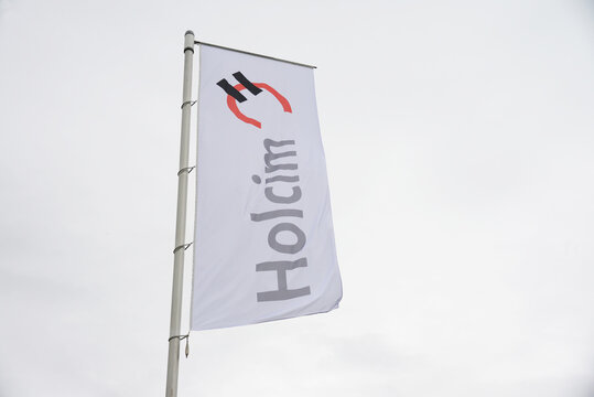 Zeithain, Saxony, Germany - September 27, 2019:  Flag with the logo of Holcim in Zeithain, Germany - Holcim is a Swiss-based global building materials and aggregates company