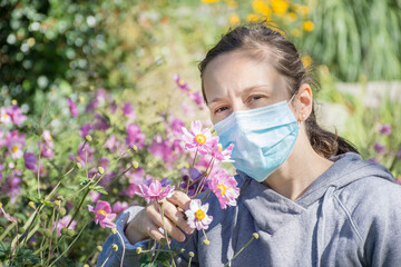 Young woman trying to smell wild flowers in the park while wearing medical mask. Conceptual photo of coronavirus or allergy, quarantine exit. Fototapete