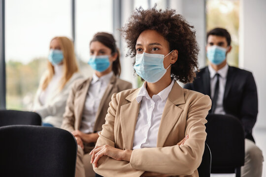 Young mixed race businesswoman sitting on seminar and listening presentation during corona virus outbreak.