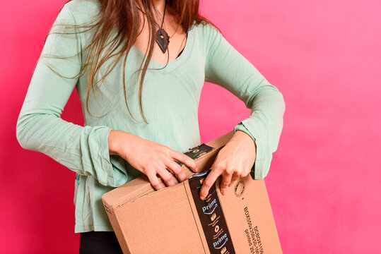 Valencia, Spain - November 28, 2020: A woman opens a cardboard box package sent by Amazon Prime.