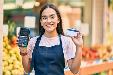 Young latin shopkeeper girl smiling happy holding credit card and dataphone at fruit store.
