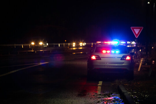 Police emergency flash lights at night from the back on highway