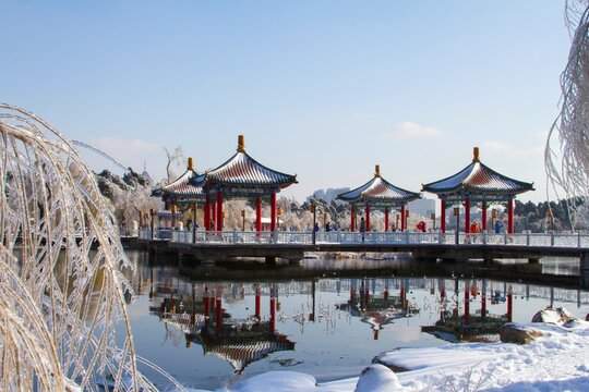A Chinese Architecture pavilion reflected in lake after storm. Winter landscape.