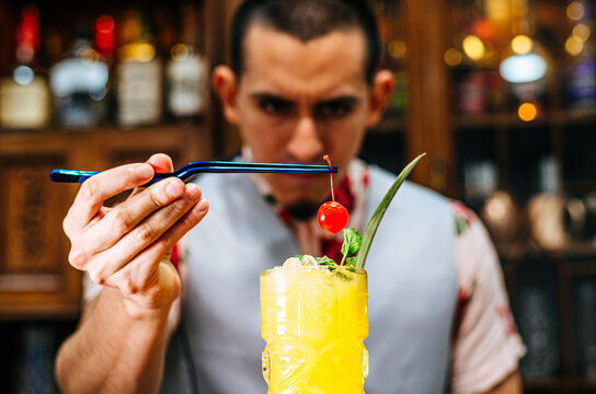 Bartender putting a cherry on a tiki cocktail.