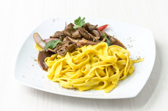 Peruvian food: Fettuccine with huancaina sauce and lomo saltado.