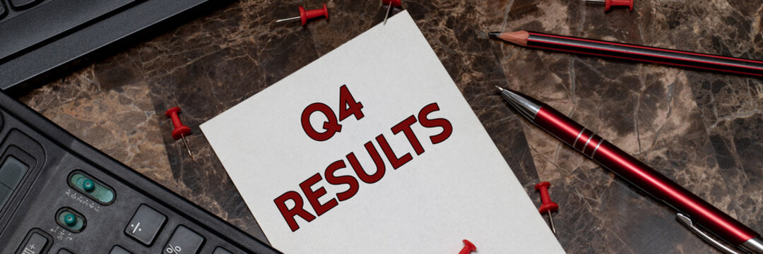 Q4 RESULTS, text is written on a sheet of notepad. Financial report at the end of the year.