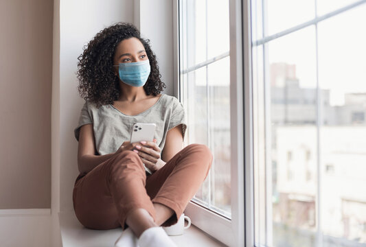 Sad woman alone during coronavirus pandemic wearing face mask indoors at home for social distancing. Anxiety, stress, lockdown, mental health crisis concept.