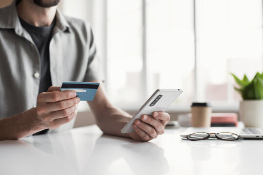 Man holding credit card and using smartphone at office, businessman shopping online, e-commerce, internet banking, spending money, working from home concept