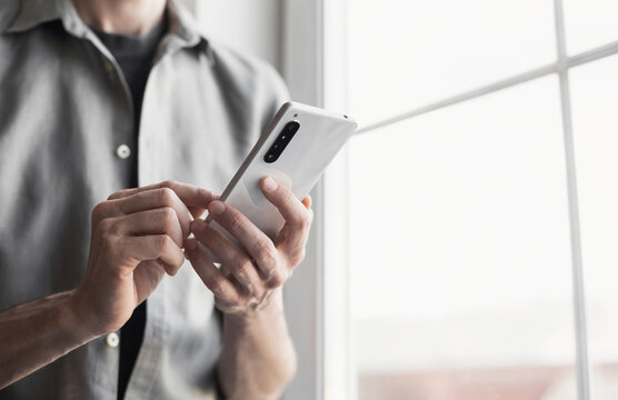 Closeup photo of male hands with smartphone. Young business man using phone at office. Communication, connection, business, people, technology concept,
