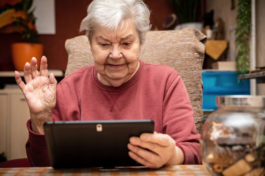 female senior adult is holding a tablet in her hands, waving with one hand to the screen