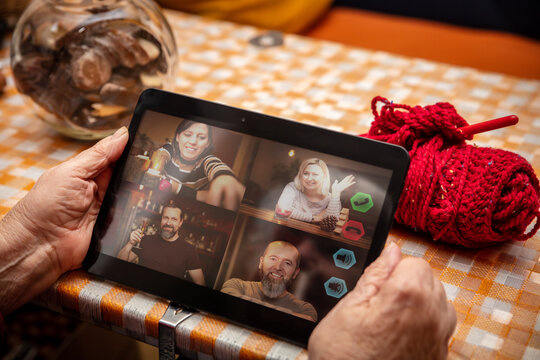 female senior adult is holding a tablet in her hands, chatting or conference with family or friends