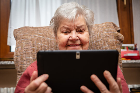 female senior adult is holding a tablet in her hands