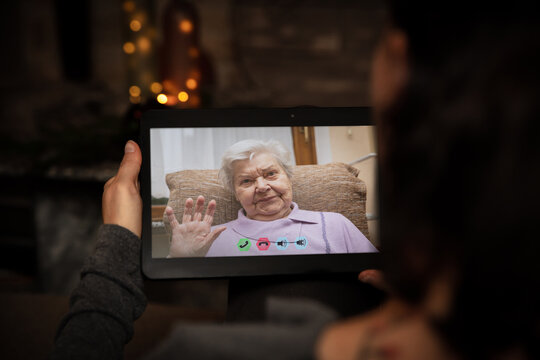 Senior adult is talking via video conference with a younger woman