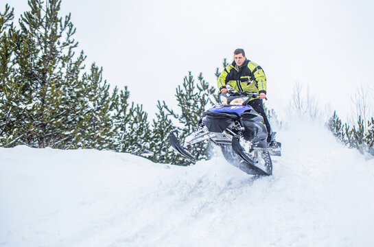 Jumping on a snowmobile on a background of winter forest. Bright snowmobile. Athlete on a snowmobile moving in the winter forest in the mountains. Man and fast action snowmobile jumping
