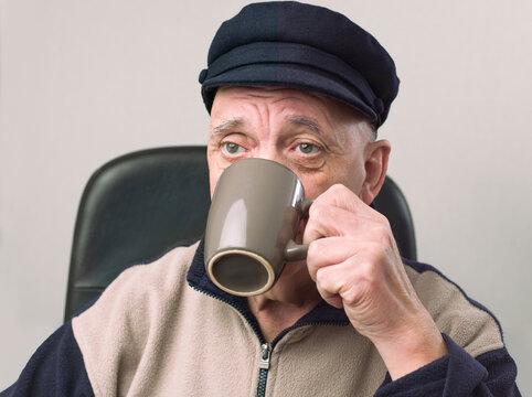 portrait vieil homme buvant une tasse de café dans son fauteuil