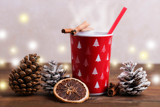 Red cup with hot drink and New Year's decor
