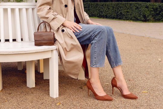 Closeup legs high heels, woman in beige coat and blue jeans with brown leather bag. Fashion