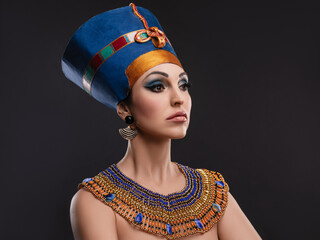 closeup studio portrait of a beautiful woman with brown eyes and evening make-up in the image of Queen Nefertiti, crown, necklace